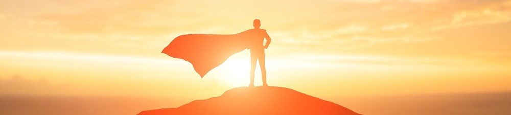 Person in a flowing cape standing on top of a hill