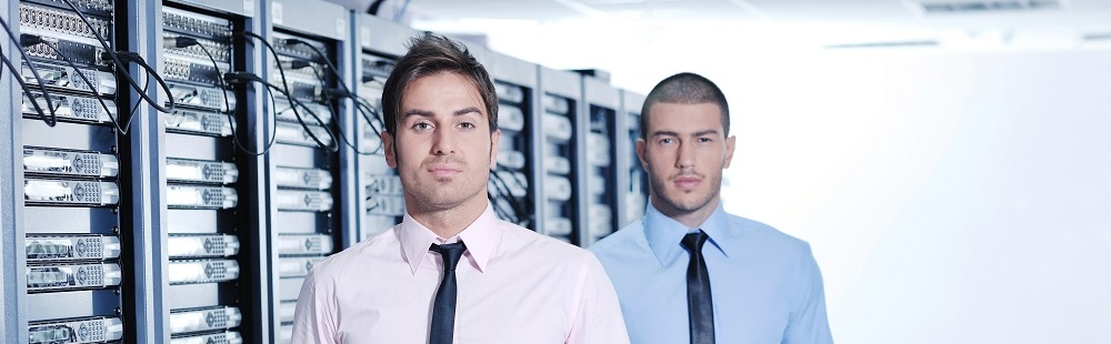 Two IT guys standing in front of a row of servers