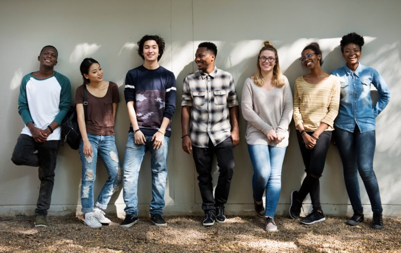 Group of people laughing together against a wall.
