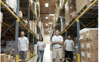 Four employees standing amongst boxes in a warehouse