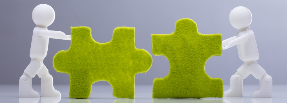 Two green puzzle pieces being pushed together